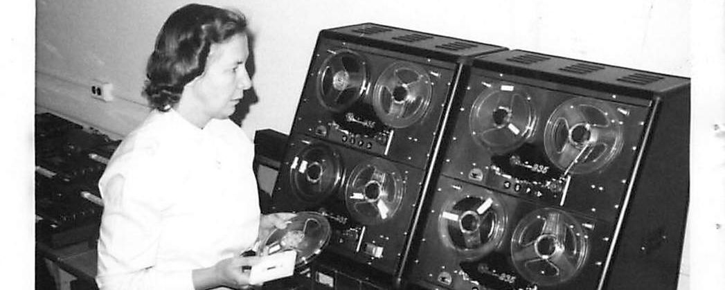 A woman standing near a big audio recording machine