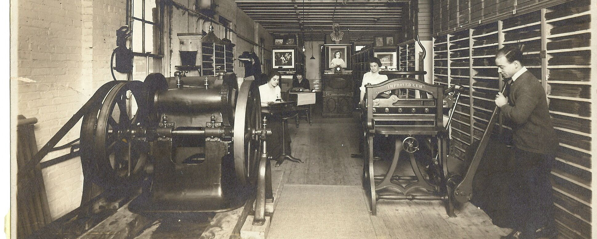 Print shop shown with big machines and people working with transcribers