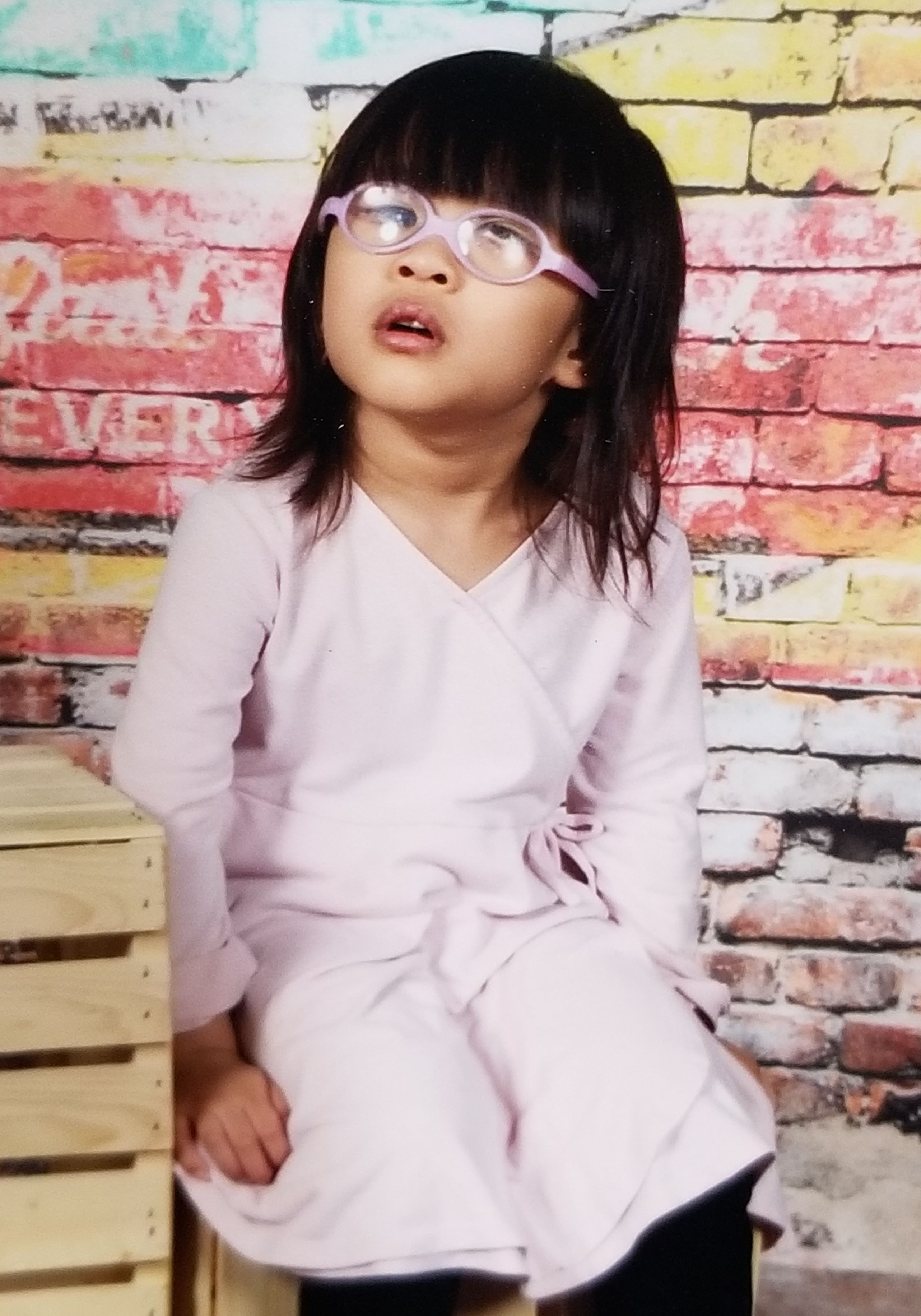 Clara pictured wearing a long sleeved pink dress and pink glasses