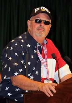 Dwight pictured at a podium wearing an American flag shirt and Air Force hat