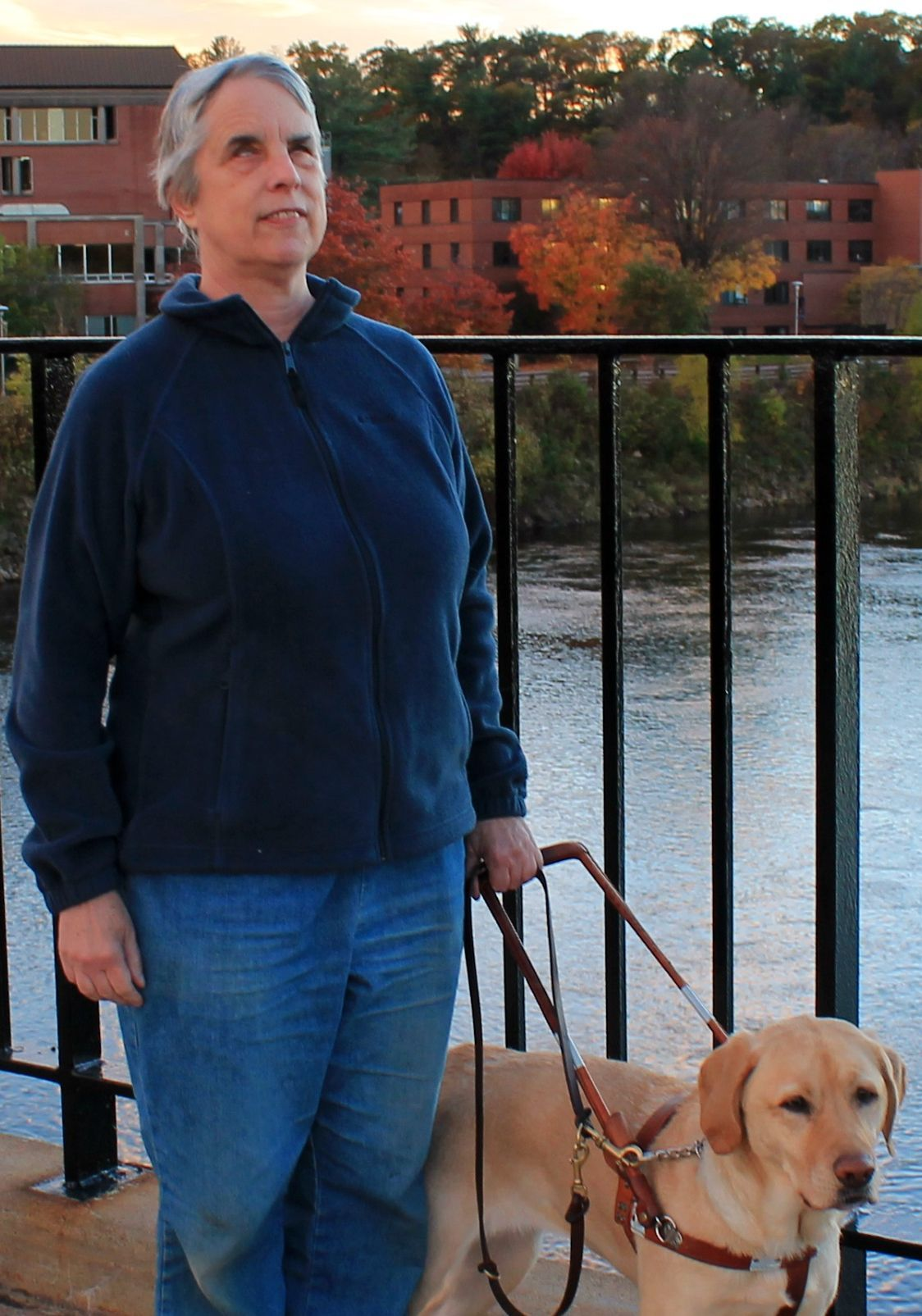 Dr. Kathie pictured with her guide dog on a bridge over a body of water