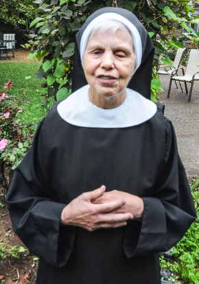 Sister Dolores pictured in her habit with her hands clasped in her convent's garden